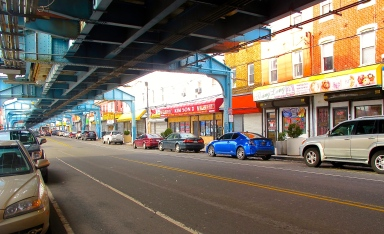 Below the El, Kensington Avenue is lined with numerous businesses and apartments.